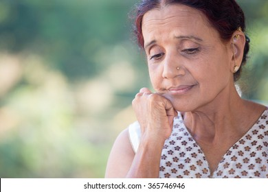 Closeup portrait, morose elderly lady, downcast gloomy, resting face on hand, isolated green outdoors background