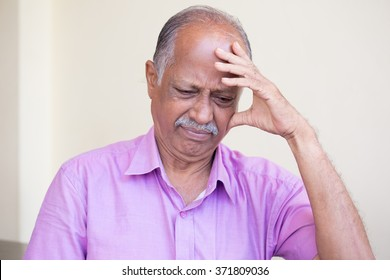 Closeup portrait, morose elderly pensioner, downcast gloomy, resting hand on head, isolated indoors home background