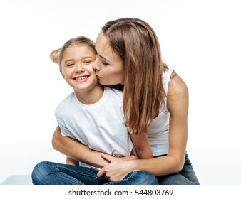 Close-up portrait of mother hugging and kissing cute smiling daughter isolated on white