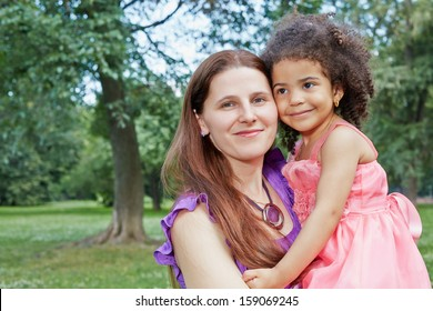 Closeup portrait of mother who holds her little daughter in her arms, standing in park on summer day