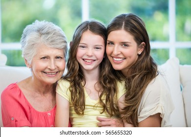 Close-up portrait of multi-generation family sitting on sofa at home