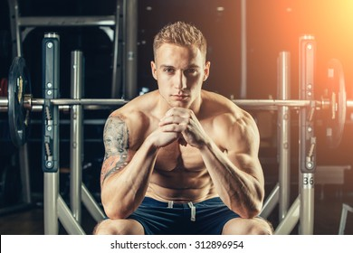 Closeup portrait of a muscular man workout with barbell at gym. He is sitting in the frame view, thinking.