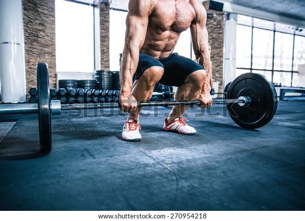 Nahaufnahme eines Porträts eines Muskeltrainings mit Barbell im Fitnessraum