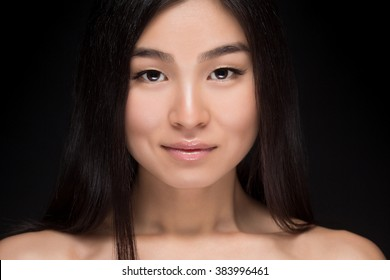 Close-up portrait of naked Asian woman smiling and looking at camera. Happy lady with long black hair posing in studio isolated on dark background.