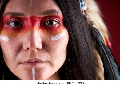close-up portrait in native american style, beautiful woman in Indian hat and drawings on face, trendy color photo. accessories Bohemians and Boho