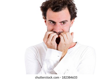 Closeup portrait nerdy, shy, confused young guy, looking scared, shocked man biting nails, avoiding eye contact, craving something isolated white background. Human emotion facial expression, reaction