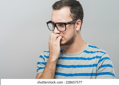 Closeup portrait of a nerdy young guy with glasses biting his nails
