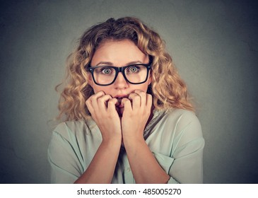 Closeup portrait nervous stressed young woman biting fingernails looking anxiously craving isolated gray background. Human emotion face expression feeling