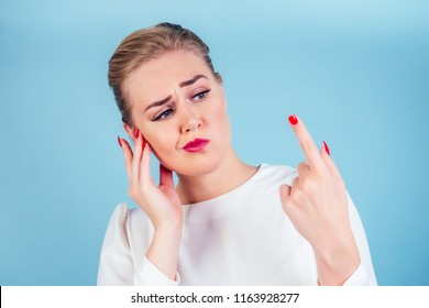 close-up portrait of nervous unhappy young blonde woman looking at a broken fingernail and crying . red long nails manicure broken nail blue background in studio