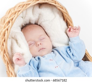 Close-up portrait of newborn baby sleeping sleeps in basket with towel. Beautiful baby sleeping on white in studio isolated over white background.