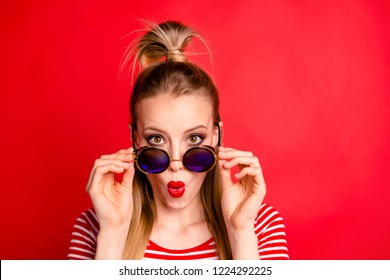 Close-up portrait of nice astonished lovely glamorous charming attractive magnificent girl with pigtail pony-tail putting down sun glasses plump lips isolated over bright vivid red background