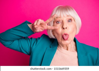 Close-up portrait of nice attractive cheerful funky gray-haired lady wearing blue jacket showing v-sign near eye tongue out fooling isolated on bright vivid shine vibrant pink fuchsia color background