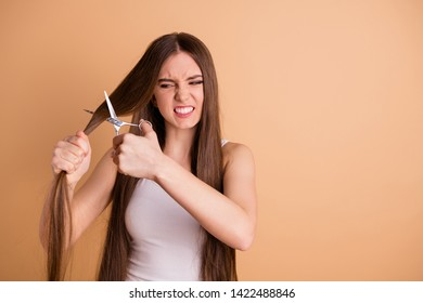 Close-up portrait of nice attractive crazy evil moody grumpy lady cutting messy thin weak curls ends oil recovery season spring moisturizing nourishing therapy treatment isolated on beige background