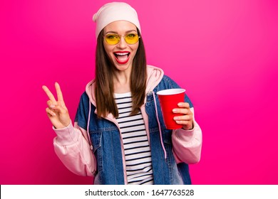 Close-up portrait of nice attractive lovely pretty cheerful cheery girl holding in hand tasty yummy coffee cup showing v-sign isolated on bright vivid shine vibrant pink fuchsia color background