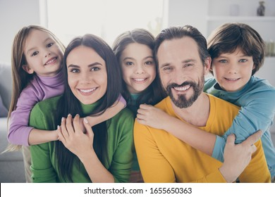 Close-up portrait of nice attractive lovely ideal friendly affectionate cheerful cheery family three pre-teen kids mom dad embracing at light white interior style house apartment indoors