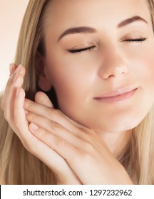 Closeup portrait of a nice blond girl with closed eyes with pleasure applying facial cream, using natural beauty treatment, health and beauty care concept