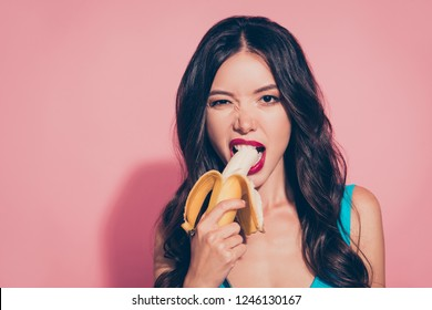 Close-up portrait of nice cheeky cunning adorable glamorous charming attractive wavy-haired lady holding biting banana red lips isolated over pink pastel background