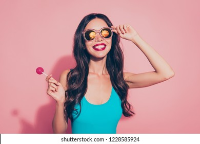 Close-up portrait of nice cheerful dreamy cute lovely sweet adorable charming attractive wavy-haired lady with tasty yummy sugary lolly pop red lips eyeglasses eyewear isolated over pink background