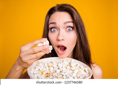 Close-up portrait of nice cute funky attractive cheerful positive girl grasping pop-corn in hand having fun isolated over bright vivid shine yellow background