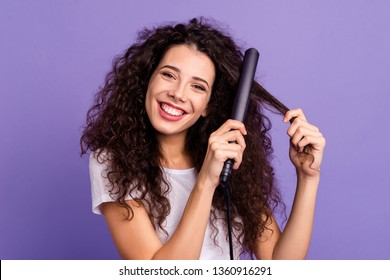 Close-up portrait of nice cute lovely well-groomed attractive cheerful wavy-haired lady using new electric high temperature ironer curls isolated on bright vivid shine violet pastel background