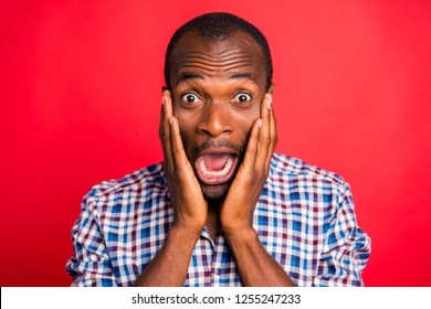 Close-up portrait of nice handsome attractive scared afraid guy wearing checked shirt holding cheeks in hands opened mouth isolated over bright vivid shine red background