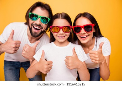 Close-up portrait of nice lovely attractive cheerful glad people having fun day wearing colorful modern eyeglasses eyewear recommend showing thumbup isolated over shine vivid pastel yellow background