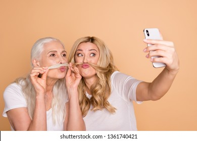 Close-up portrait of nice lovely attractive charming cute cheerful cheery playful comic foolish crazy ladies wearing white t-shirt taking making selfie curls isolated on beige pastel background