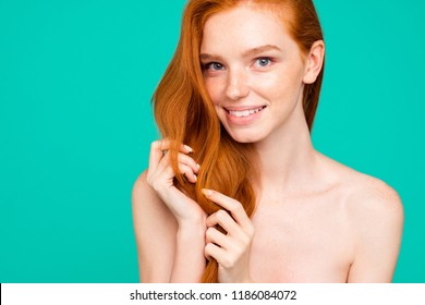 Close-up portrait of nice nude positive sweet tender nice cheerful red-haired girl with shiny pure clean clear fresh smooth flawless skin, touching hair, isolated over green turquoise background