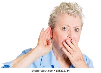 Closeup portrait, nosy, funny senior mature woman, hand to ear, trying to listen to juicy gossip conversation and shocked from hearing news. Privacy violation, isolated white background