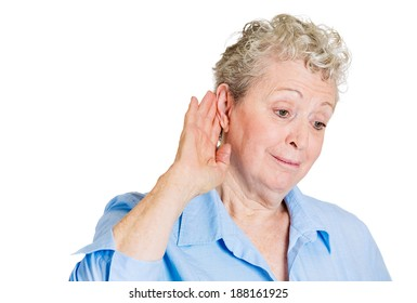 Closeup portrait, nosy, surprised senior mature woman hand to ear trying to secretly listen in on juicy gossip, conversation, news, happy what she hears, privacy violation, isolated white background
