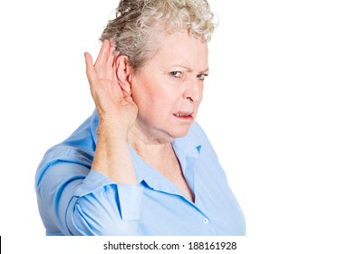 Closeup portrait, nosy worried funny senior mature woman, hand to ear, trying to listen to juicy gossip conversation and mad angry from hearing bad news. Privacy violation, isolated white background