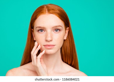 Close-up portrait of nude calm red-haired girl with shiny pure clean clear fresh smooth flawless perfect skin, touching face, spa, therapy, treatment, isolated on green turquoise paste teal background