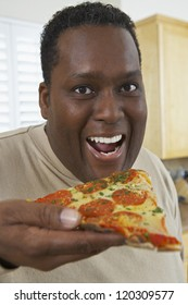 Close-up portrait of an obese African American man eating slice of pepperoni pizza