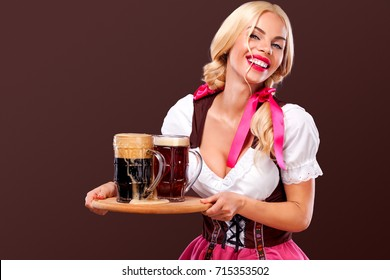 Closeup portrait of Oktober fest girl - waitress, wearing a traditional Bavarian dress, serving big beer mugs on brown background.