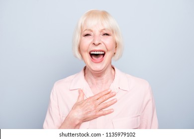 Closeup portrait of old adult caucasian blonde glad cheerful amazed surprised lady smiling, opened mouth, over grey background, isolated