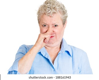 Closeup portrait old lady, senior executive, grandmother, disgust on her face, pinching nose something stinks, displeased with situation, isolated white background. Interpersonal conflict