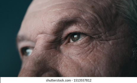 Close-up portrait of an old man. Eyes of an elderly man close-up in profile. A grown man looks away. Cool color. 4K