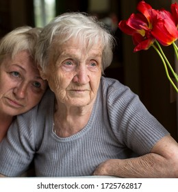 Close-up portrait of old woman with her daughter in home.