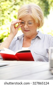Close-up portrait of old woman reading a book while sitting at home in her beautiful garden.
