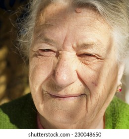 Closeup portrait of an old woman. She has a smile on her face even though she's not nice.