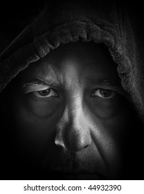 Closeup portrait of older man hidden in shadows and hood. bags under the eyes, scruffy grunge beard, wrinkles and tough looking. Black and white photograph