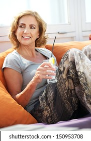 Closeup portrait of an older woman relaxing with a drink at restaurant