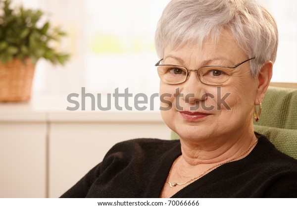 Closeup portrait of older woman wearing glasses, smiling at camera.?