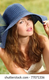 closeup portrait on fresh air of attractive young adult wearing blue hat