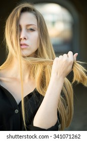 Closeup portrait of one beautiful serious cool blonde young woman with long hair outdoor looking forward on blurred background, vertical picture