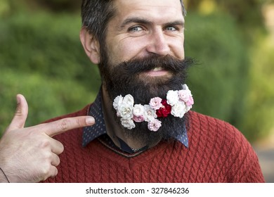 Closeup portrait of one handsome smiling man with long black beard showing on small many white and pink flowers in red sweater looking forward sunny day outdoor on natural green background, horizontal