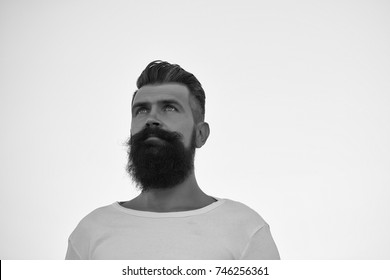 Closeup portrait of one handsome young stylish thoughtful man with long dark lush beard in white sweater looking away standing outdoor on light sky background, horizontal picture