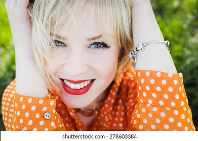 close-up portrait outdoors young beautiful girl in an orange hipster blonde bright cheerful polka dot blouse , smiling red plump lips on the background of green grass