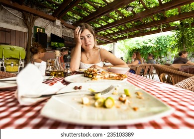 Closeup portrait of overeating woman looking at empty plates on table at restaurant