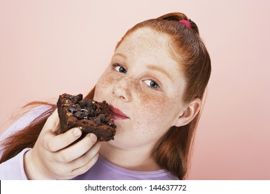 Closeup portrait of an overweight girl eating brownie